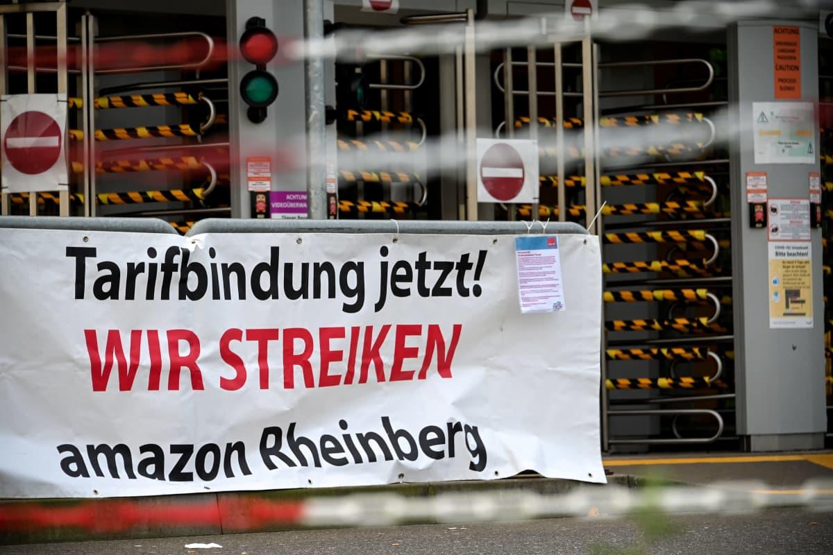 Verdi-ammattiliiton esille panema mielenosoitusjuliste Amazonin jakelukeskuksessa Rheinbergissä, Saksassa. Julisteessa vaaditaan kollektiivista neuvotteluoikeutta.