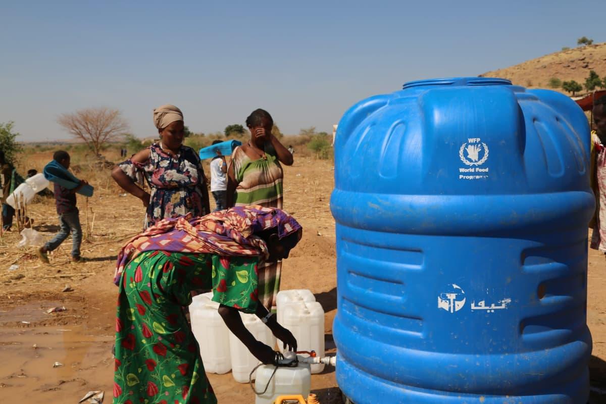 Nainen ottaa tankista vettä kanisteriin.