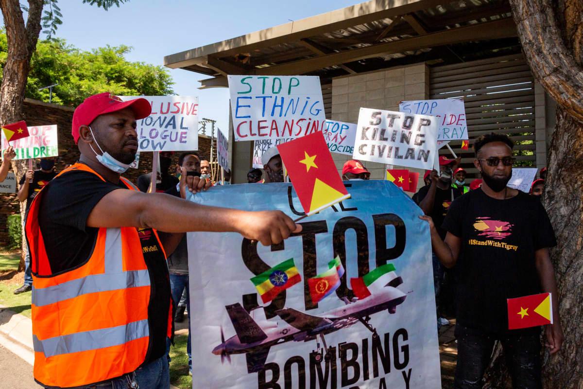Eteläafrikkalaiset Tigrayn sotaa vastustava mielenosoittajat kantavat kylttejä, joissa kehotetaan lopettamaan pommitus