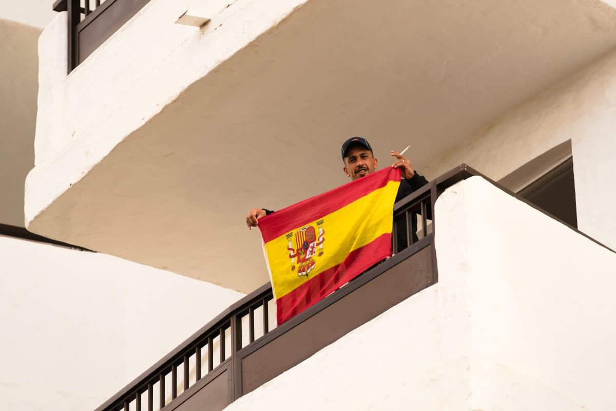 Siirtolaismies heiluttaa Espanjan lippu hotellin parvekkeella