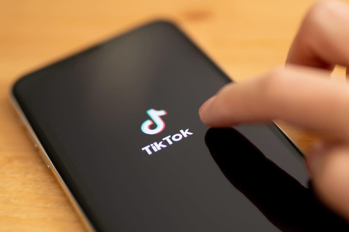 Sormi, joka osoittaa kännykän ruudulla näkyvää Tiktokin logoa.
