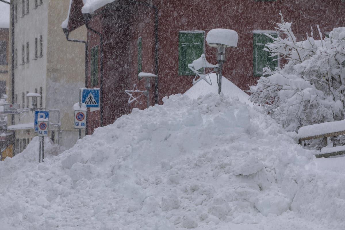 Valtava lumivuori kadulla.