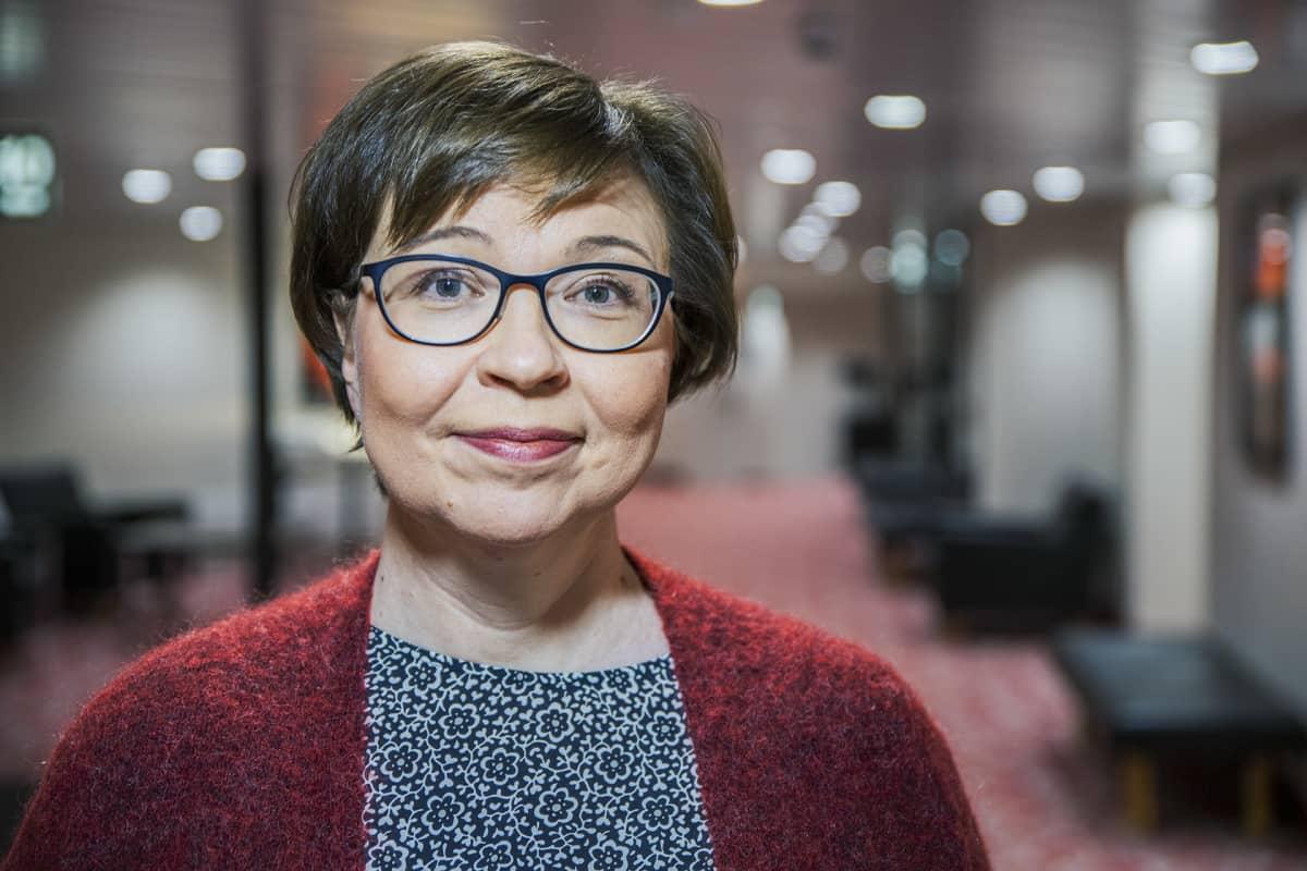 Pirjo Peräaho poseeraa kameralle hotellin käytävällä.
