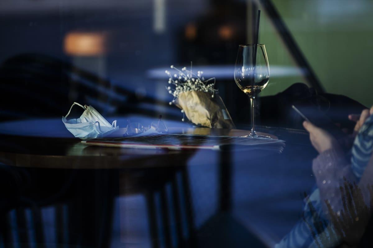 Pöydällä on kukkia, viinilasi ja kasvomaski.