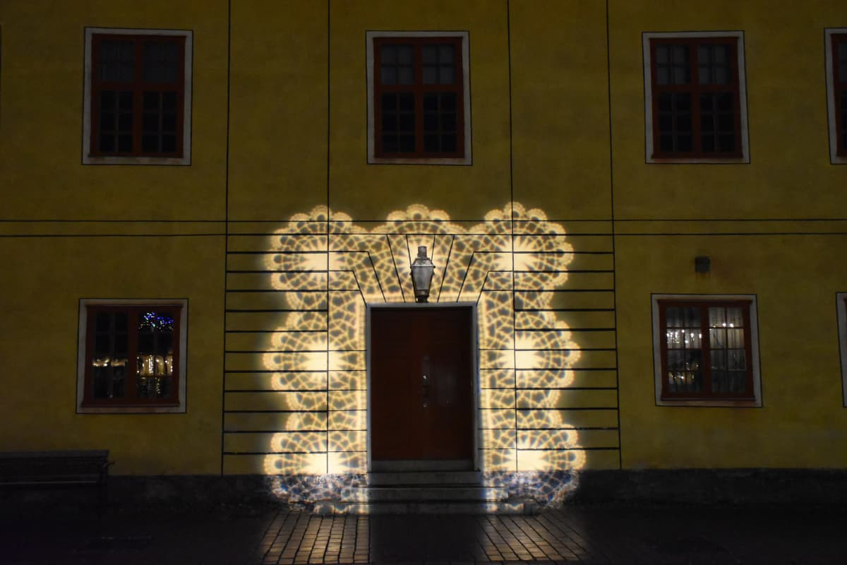 Vanhan kivitalon ovi, jonka ympärille on heijastettu valokranssi.