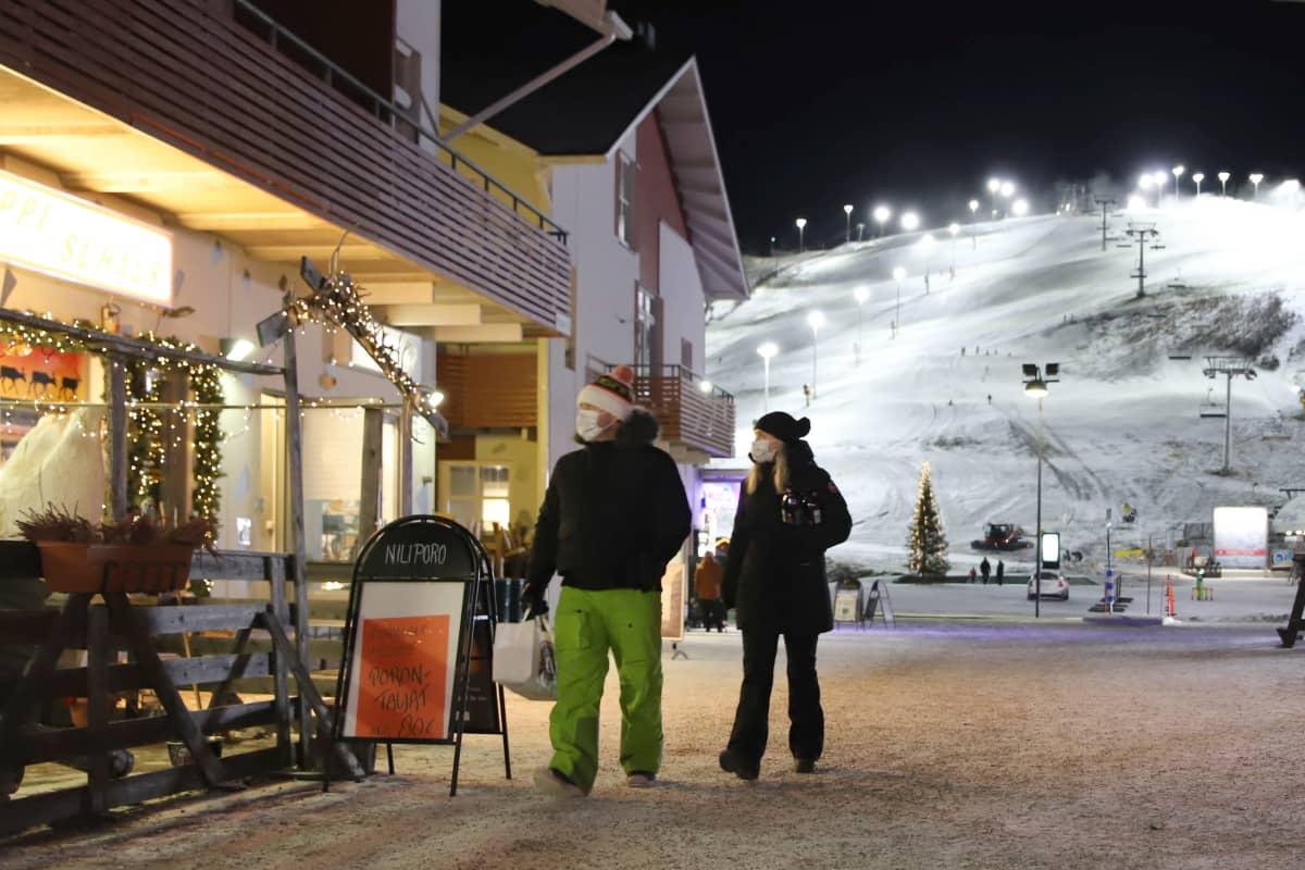 Pariskunta kävelee Levillä talvella 2020 maskit kasvoilla.