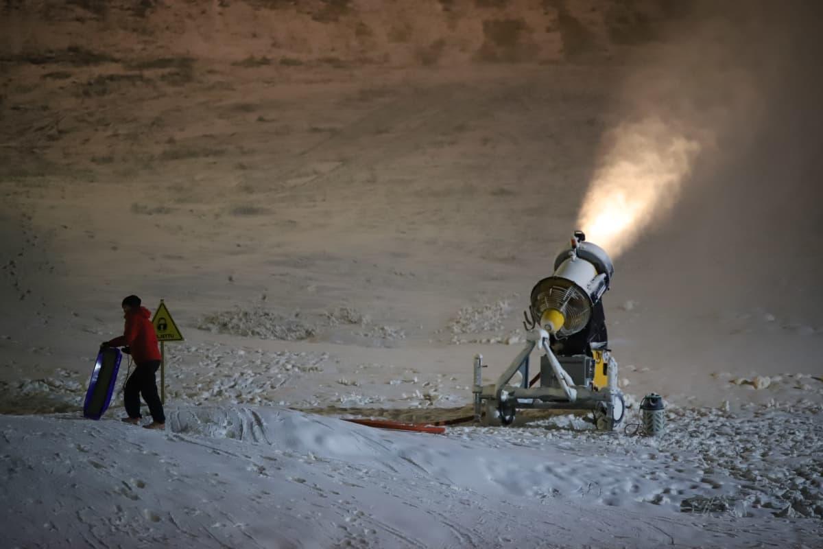 Pulkkailija Mielakan hiihtokeskuksessa lumitykin vieressä.