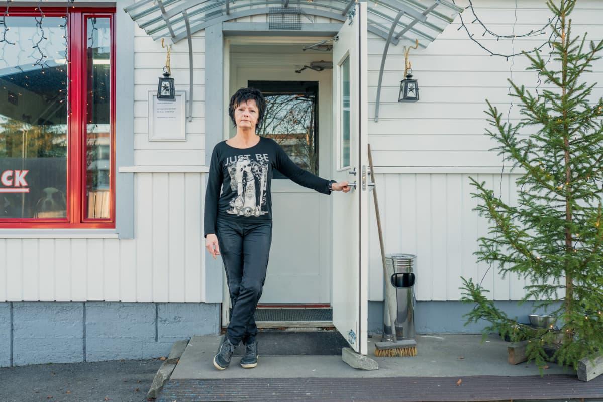 Eila Leppänen poseeraa ravintolansa ovella.