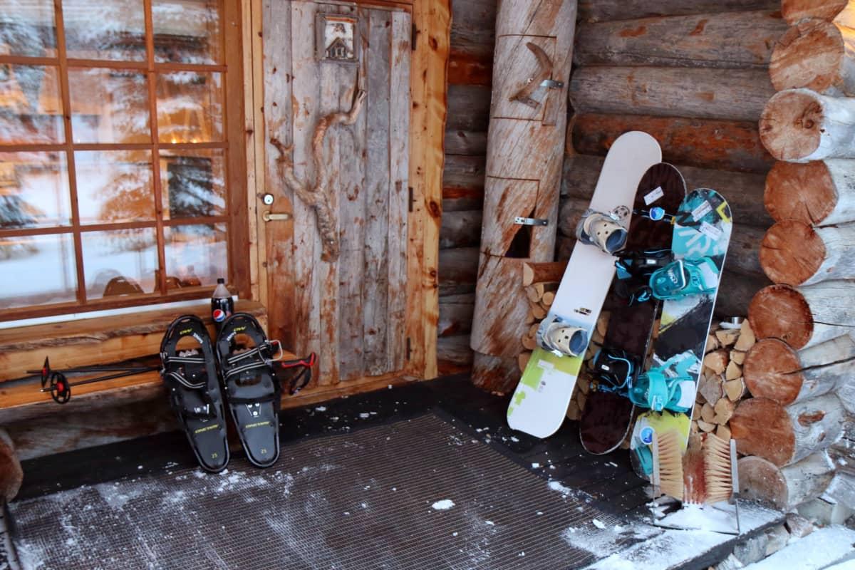 Talviurheiluvälineitä mökin terassilla.