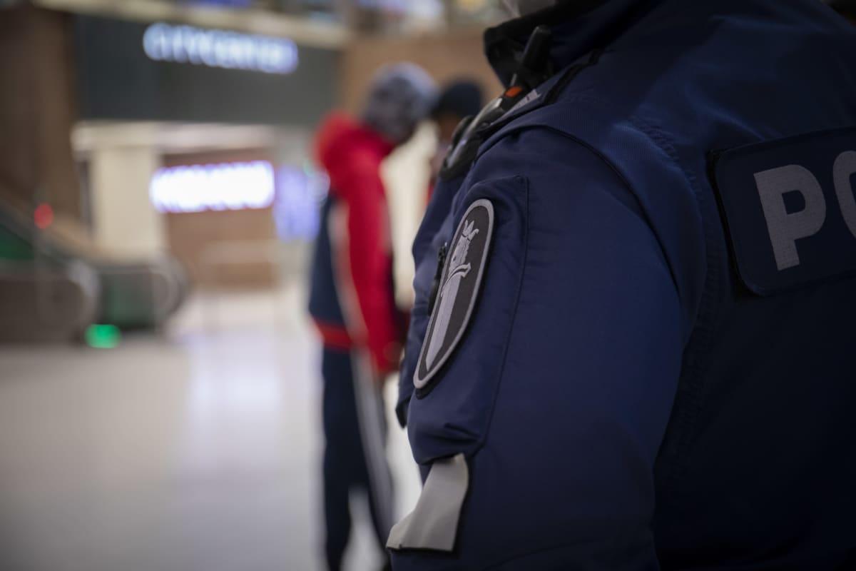 Poliisin hihamerkki, taustalla nuorehkoja henkilöitä.