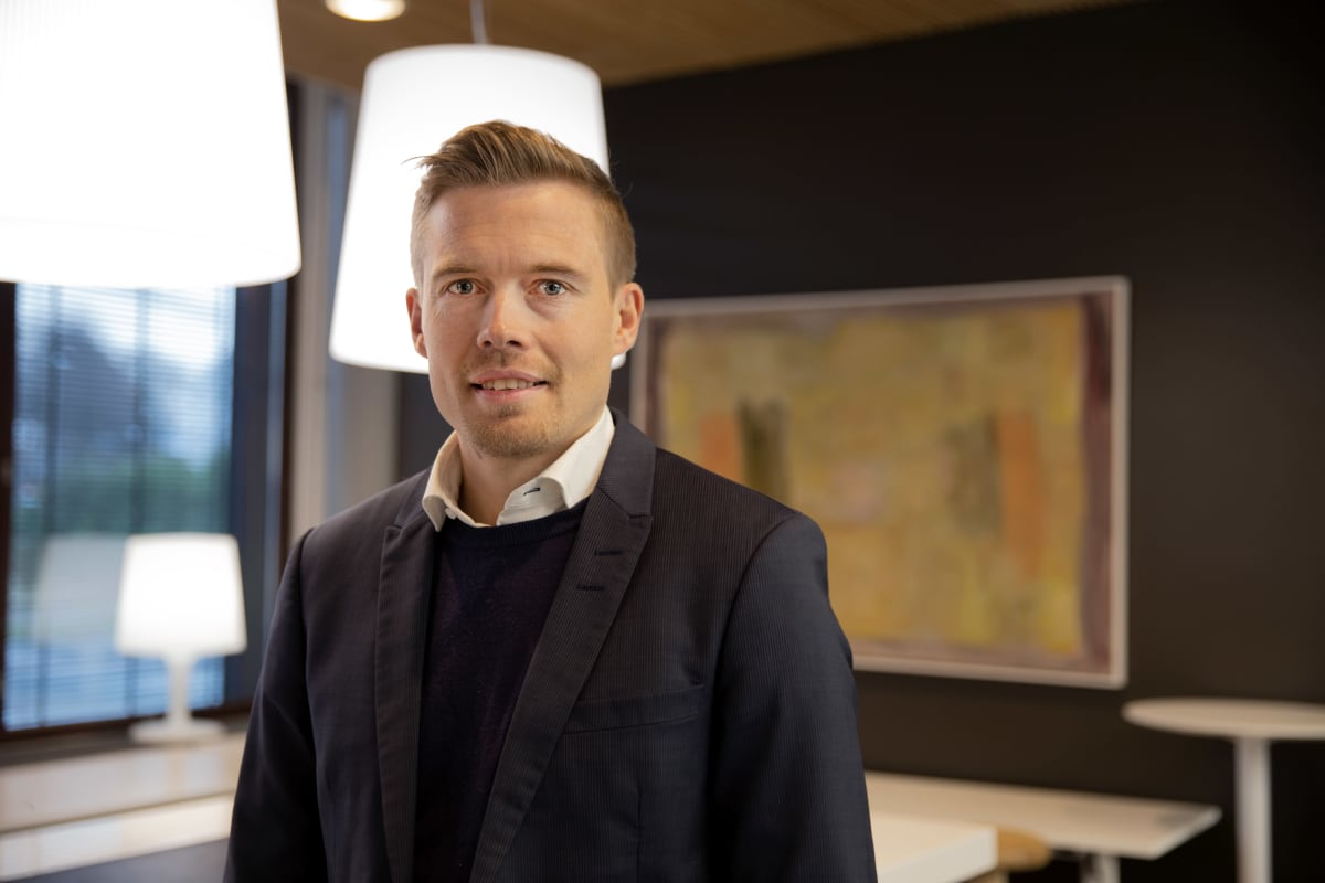 Nordean ekonomisti Juho Kostiainen seisoo pankin aulassa lähellä ikkunaa ja katsoo kameraan. Taustalla on öljyvärimaalaus.