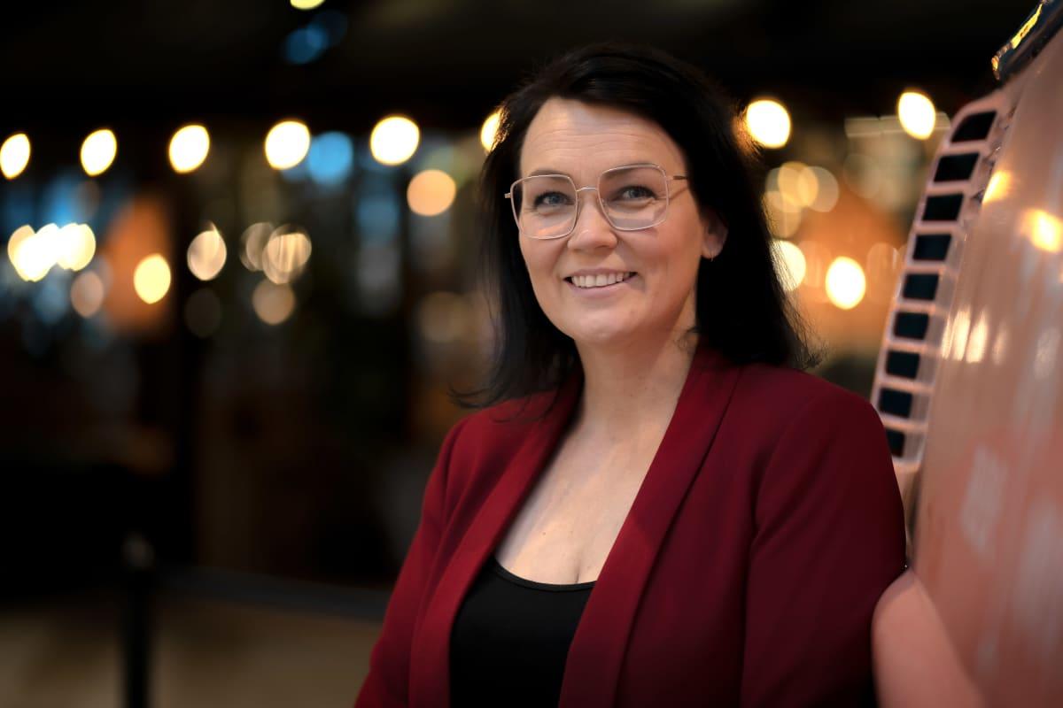 Triplan kauppakeskusjohtaja Kati Kivimäki nojaa kauppakeskuksen aulassa sijaitsevan Kleinbus-pakettiauton kylkeen ja hymyilee kameralle.