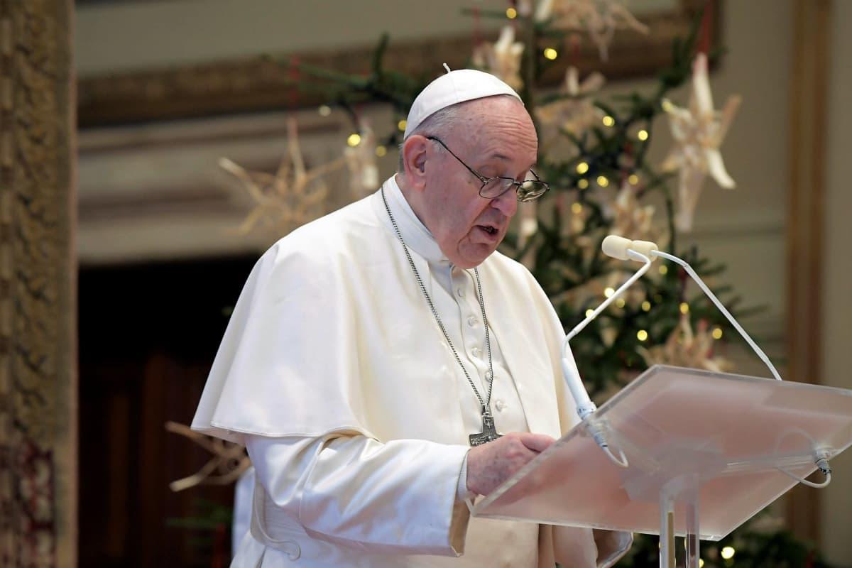 Paavi puhuu mikrofoniin. Taustalla näkyy joulukuusi.