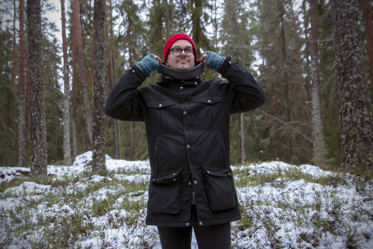 Wille Lehtovaara nostaa takin kaulusta metsässä