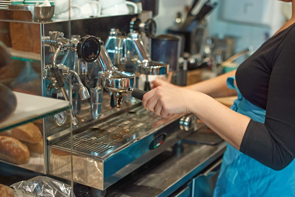 Leipomotuotteita kahvilassa, espressokeitin, kahvilatyöntekijä.