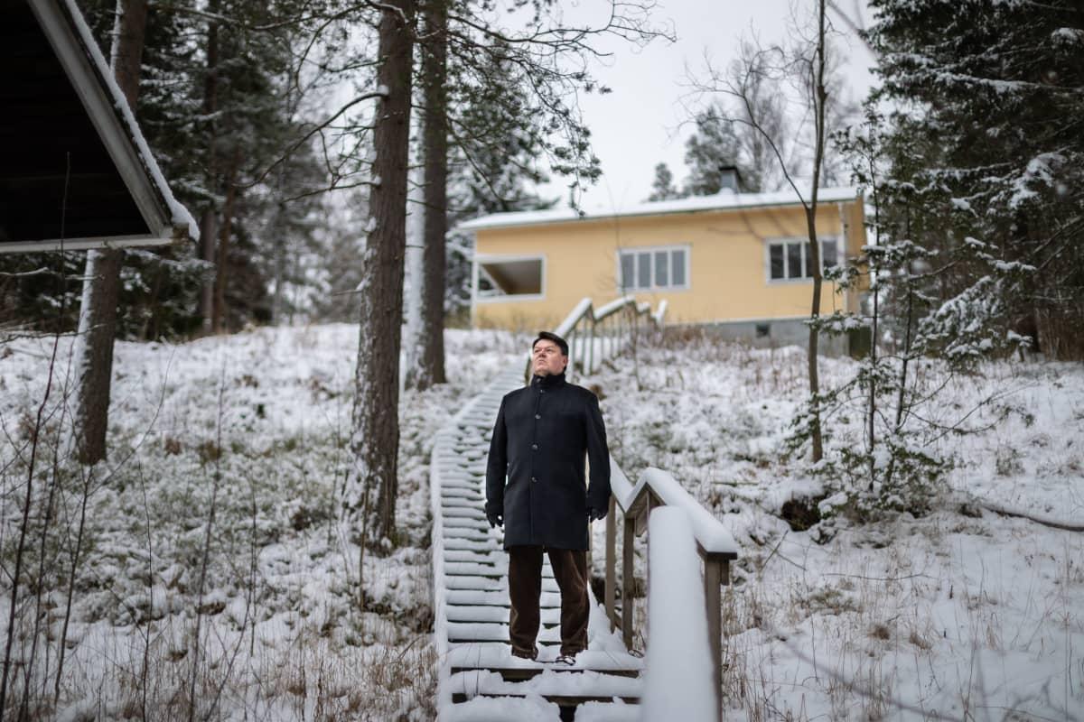 Maailman ilmatieteen järjestön pääsihteeri Petteri Taalas seisoo portailla ja katsoo kauas järvelle mökillään Nuuksiossa