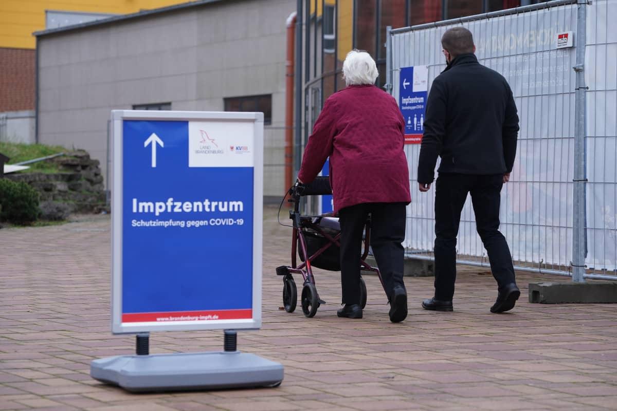 Kaksi ihmistä ohittaa kyltin jossa saksankielinen teksti Rokotuskeskus