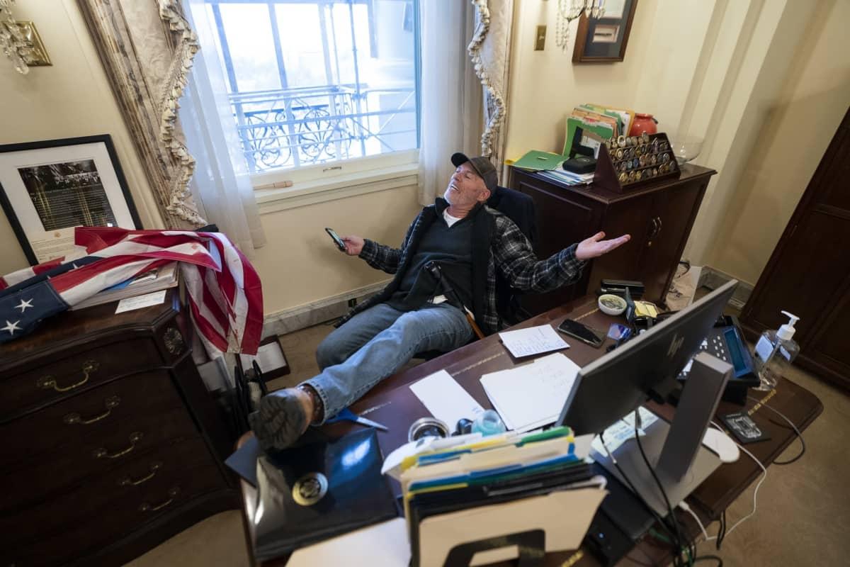 Donald Trumpin kannattaja poseerasi edustajainhuoneen puhemies, demokraatti Nancy Pelosin työpöydän ääressä.