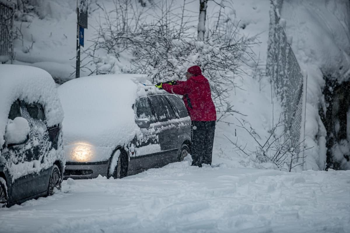 Henkilö putsaa autoa lumesta.