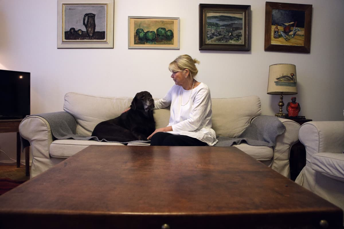 Jessica Löfgren-Eriksson istuu Luna-labrdorinnoutajansa kanssa sohvalla.