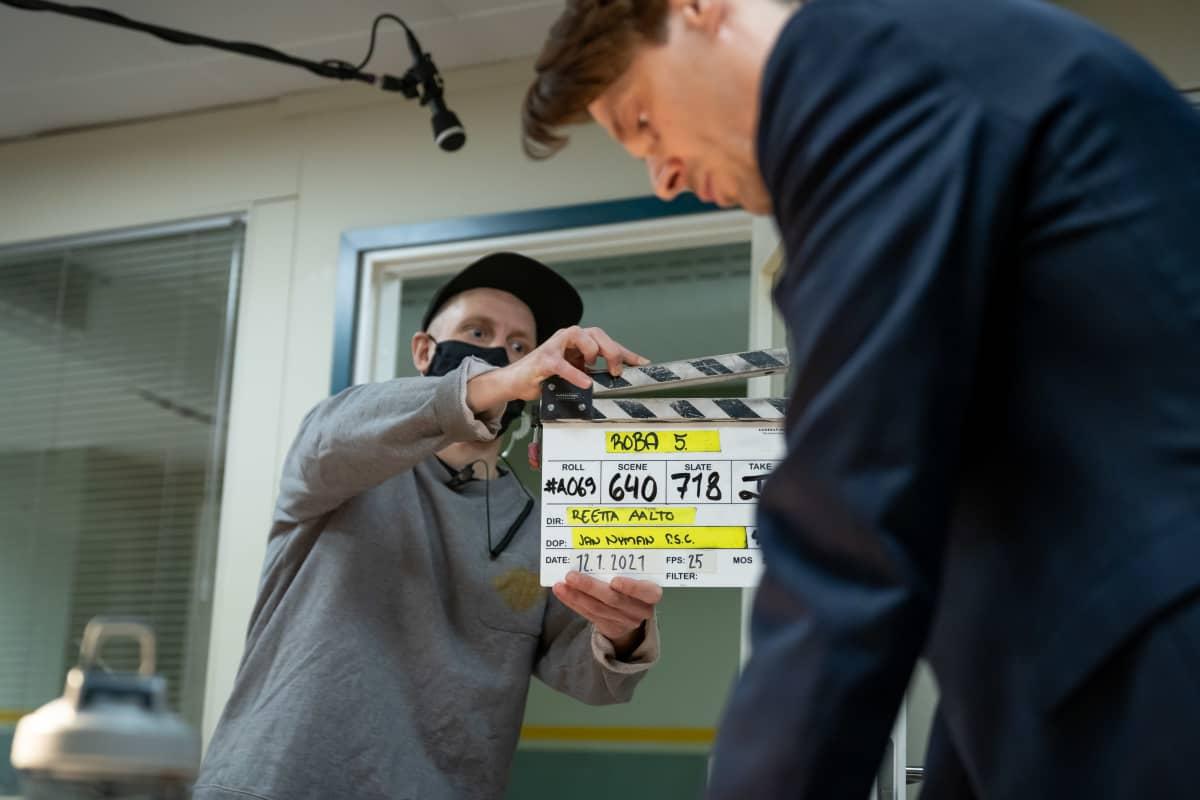 Toinen kamera-assistentti Teemu Korhonen näyttää klaffia Yellow Film & TV:n tuottaman poliisisarjan Roban kuvauksissa, oikealla näyttelijä Andrei Alén, Helsinki, 12.1.2021.