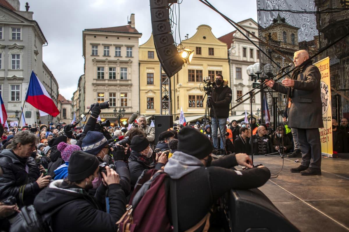 Vaclav Klaus lavalla ihmisjoukon edessä, eturivissä valokuvaajia