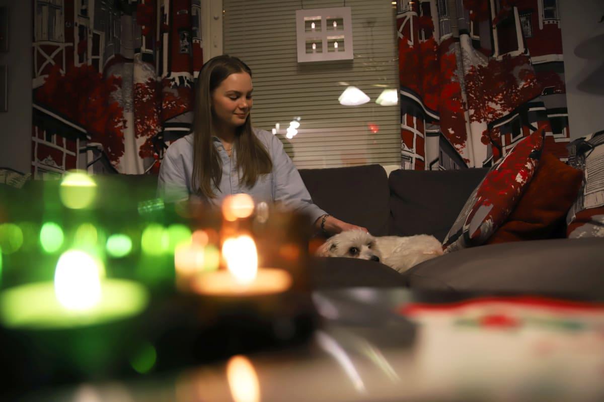 Kemiläinen, mutta Iso-Britanniassa opiskeleva Ella Heikkinen silittää koiraa.