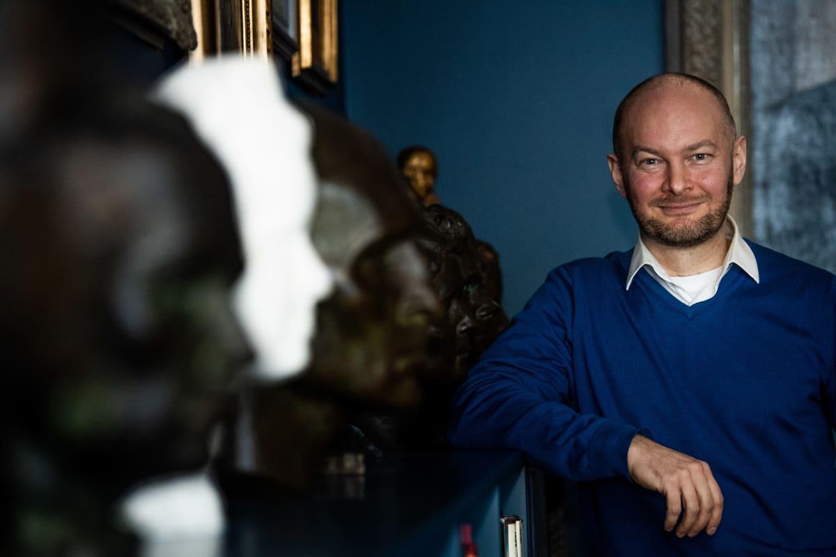Sampo Terho eri kirjailijoita esittävien patsaiden kanssa.