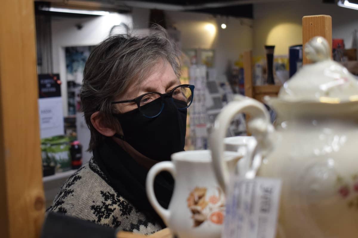 Kankaanpääläinen kirpputoriharrastaja Kristiina Capparelli Myyntitalo Jerassa astioita katselemassa.