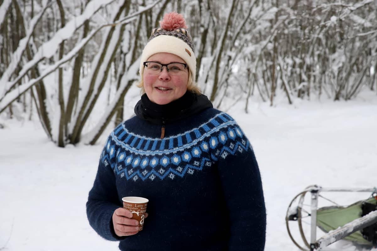 Huskyfarmi Koira Kikan yrittäjä Kirsi Översti katsoo kameraan mehumuki kourassaan