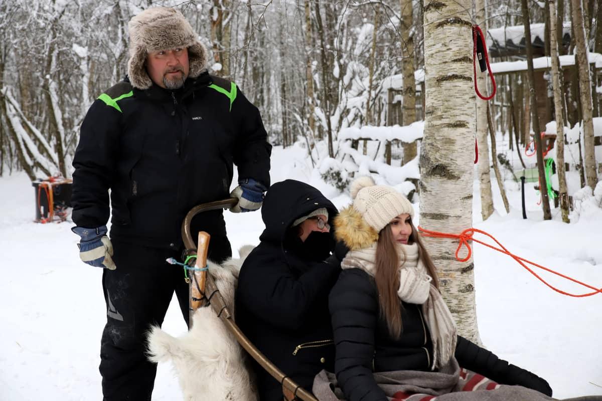 Koiravaljakolla ohjastaja ja kaksi kyytiläistä valmiina matkaan