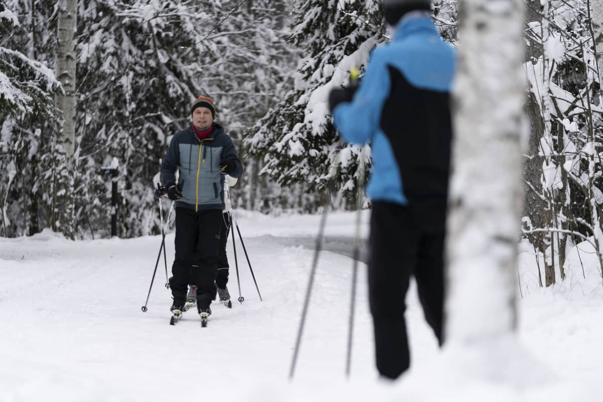Pariskunta hiihtää peräkanaa Maunulan ulkoilureitillä. Etualalla toinen hiihtäjä lähdössä lenkille.
