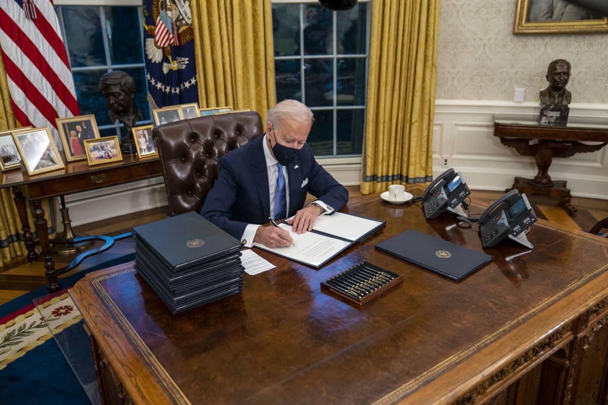 Joe Biden allekirjoittamassa asetuksia työhuoneessaan Oval Officessa.