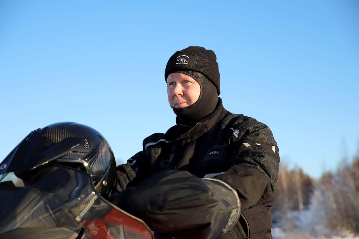Matti Simola istuu varusteissaan moottorikelkan päällä