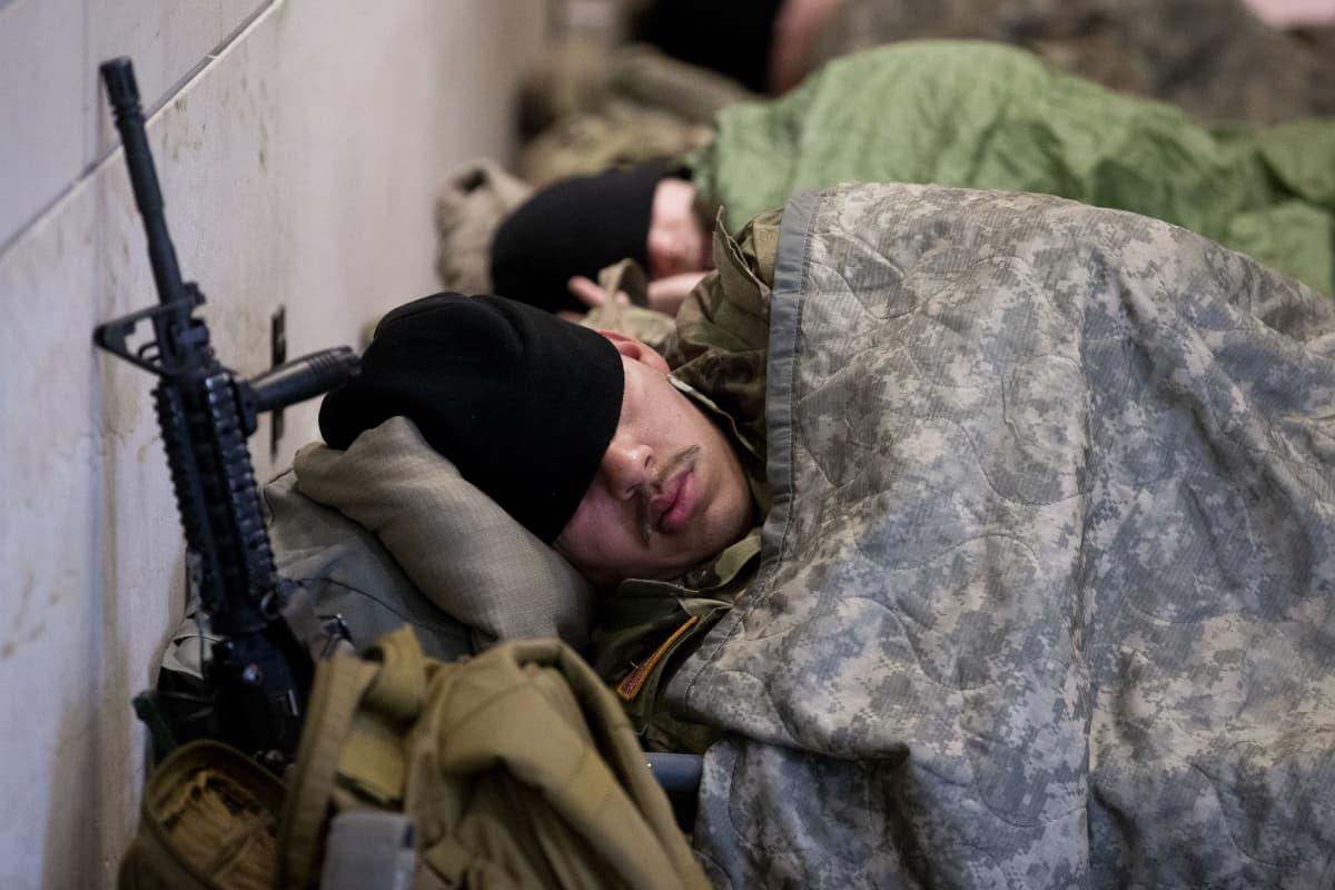 Maastopukuinen kansalliskaartin sotilas nukkuu kongressitalolla.