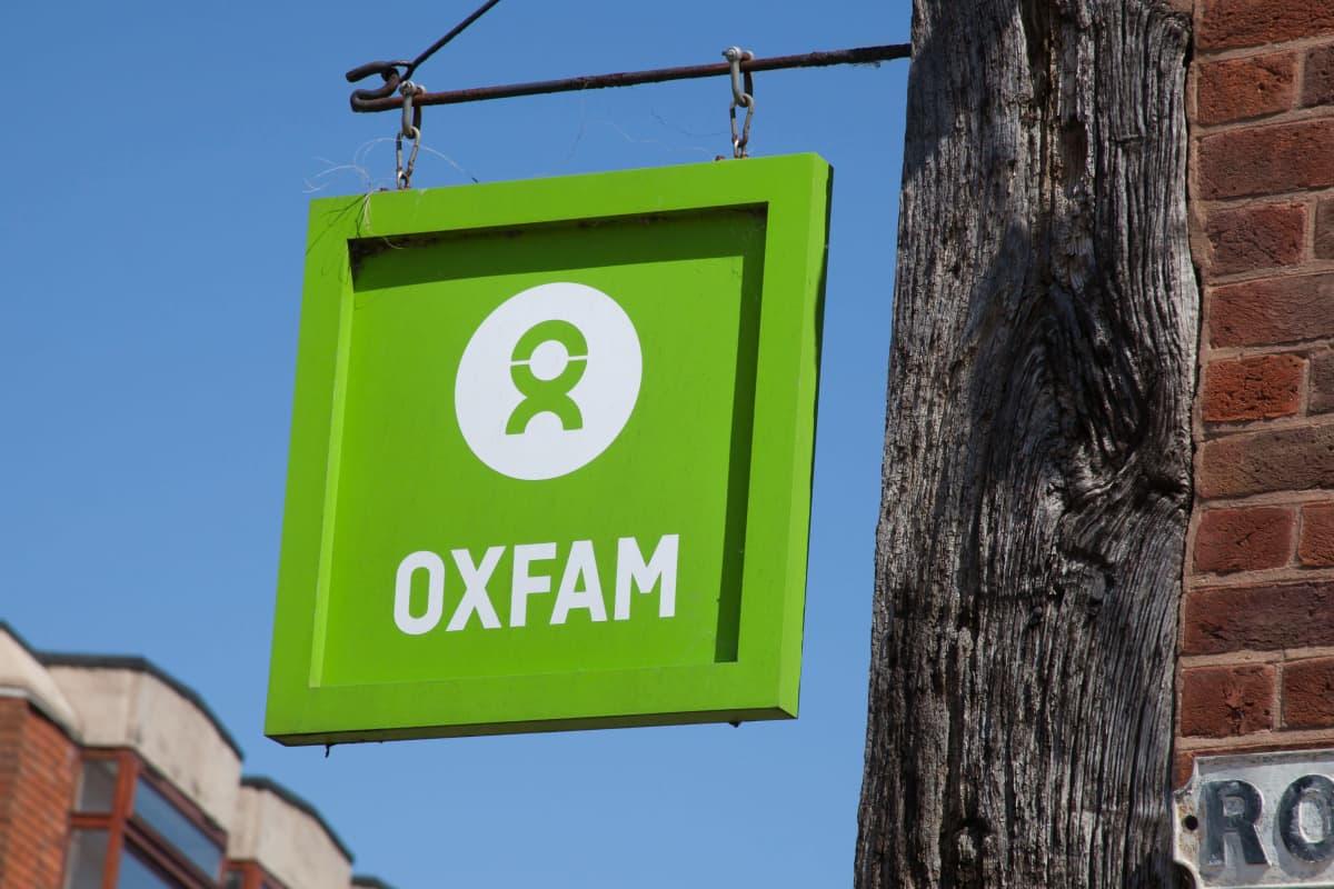 Oxfamin vaaleanvihreä kyltti roikkuu metallikiinnittimistä seinällä, kuvattuna sinistä taivasta vasten.