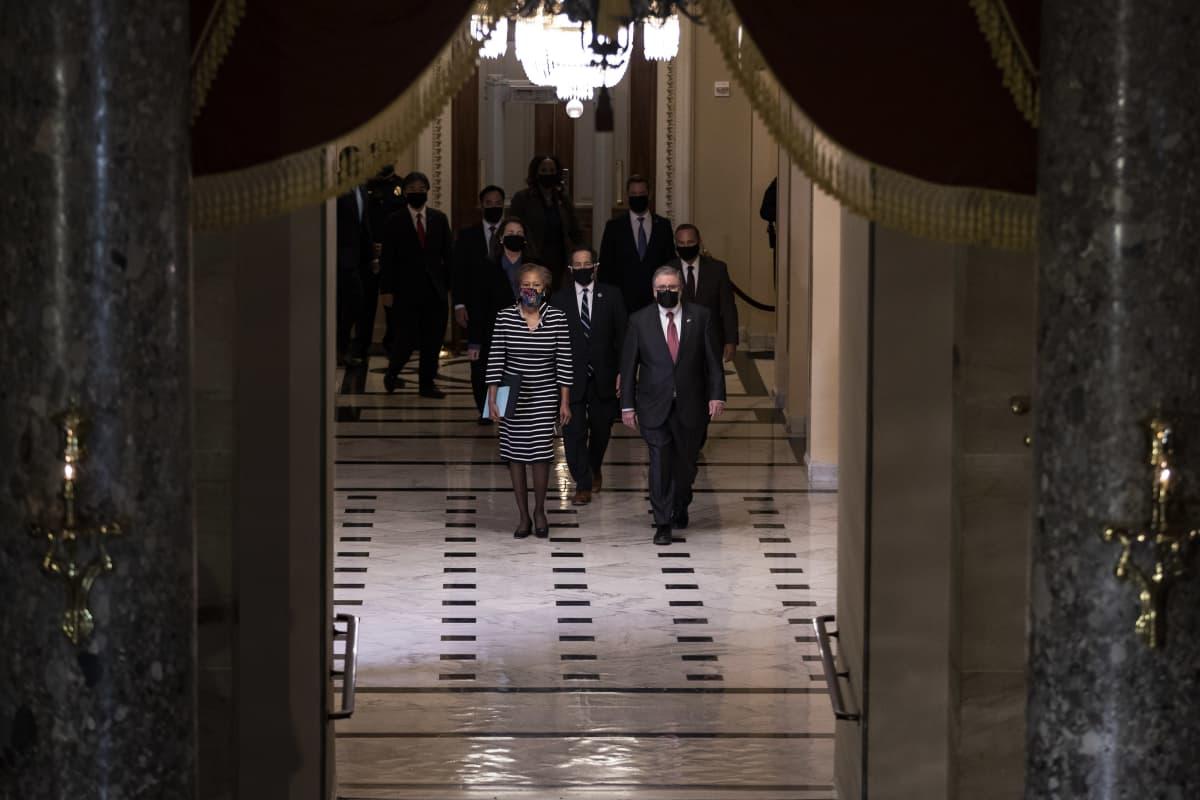 Edustajainhuoneen jäsenet marssivat kongressin käytävällä virkarikossyytteen kanssa kohti senaattia.