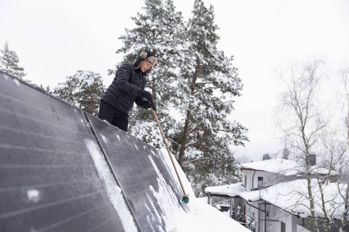 Espoolainen Ari Siipivirta pyyhkii lunta aurinkopaneelien päältä.