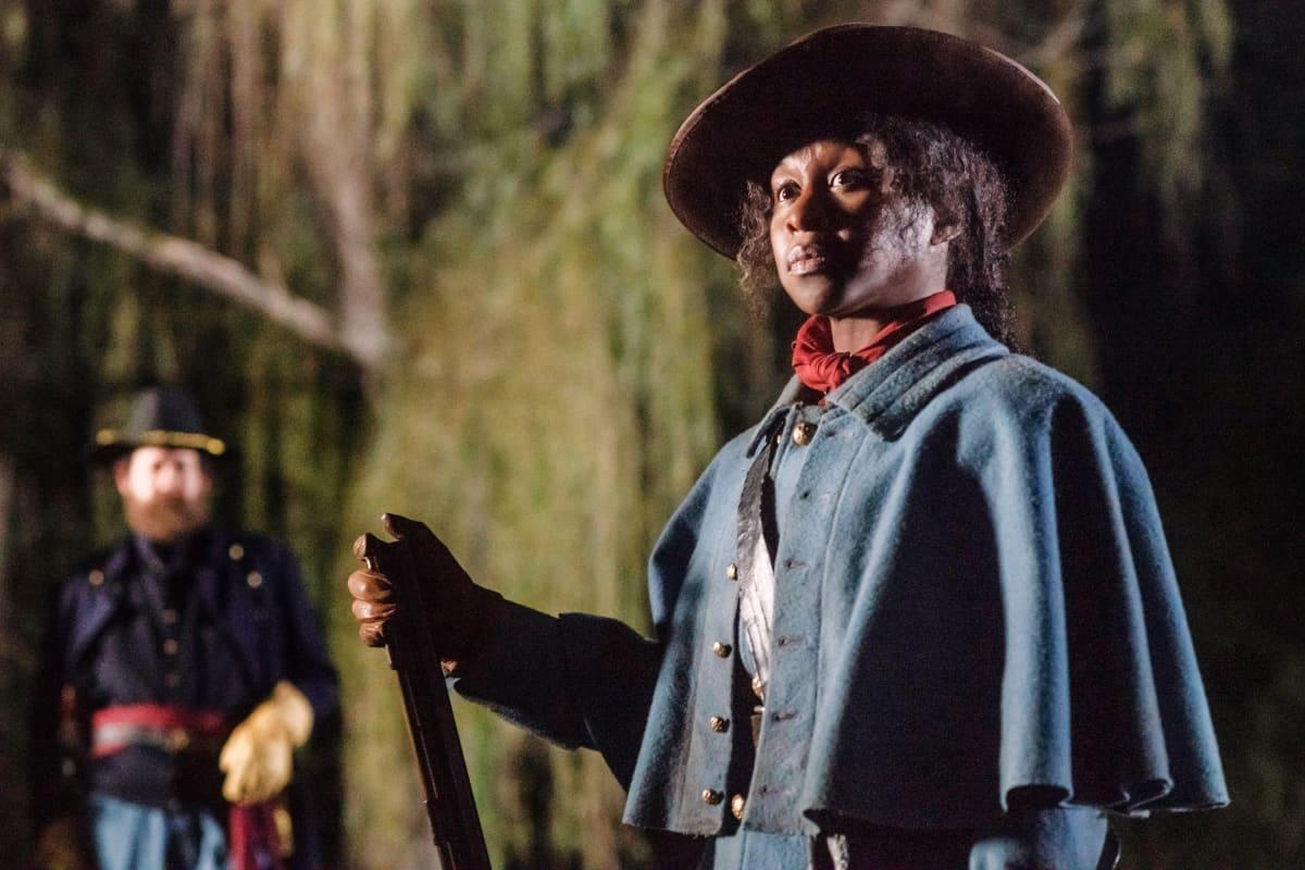Harriet Tubmania esittävä Cynthia Erivo seisoo pohjoisvaltioiden univormussa ja hattu päässään taustallaan öinen metsämaisema. Taustalla näkyy pohjoisvaltioiden upseeri.