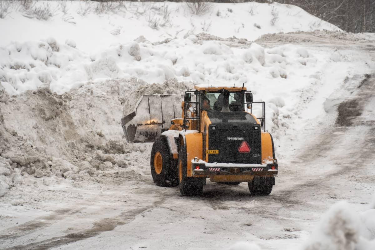 Pyöräkuormaaja tekee lumitöitä Aarikkalan lumenvastaanottopaikalla Tampereella.
