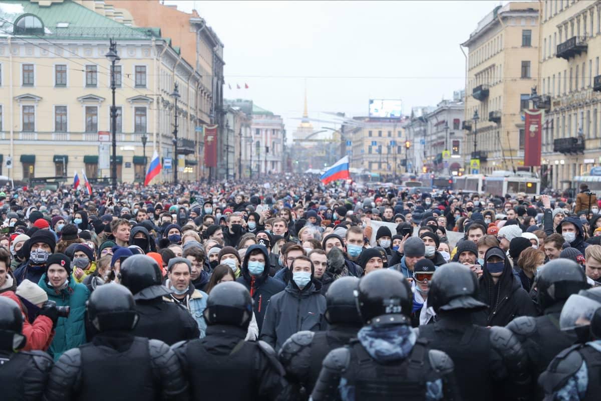 Suuri mielenosoittajajoukko, etualalla mellakkapoliiseja
