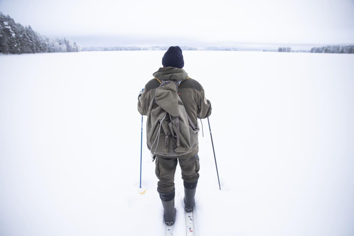 Mies hiihtää järvenjäällä.