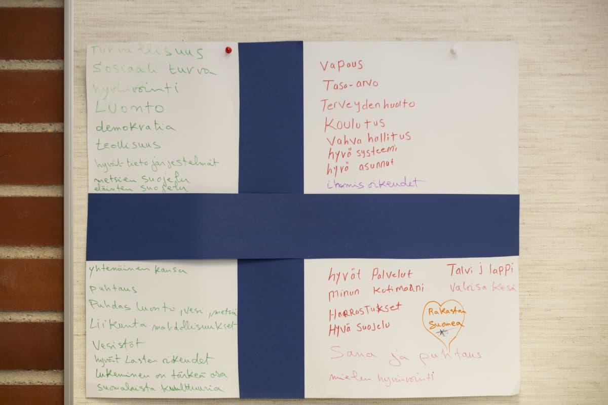 Kielikurssin vanhemmat ovat askarrelleet Suomen lipun ja listanneet siihen maan hyviä ominaisuuksia.