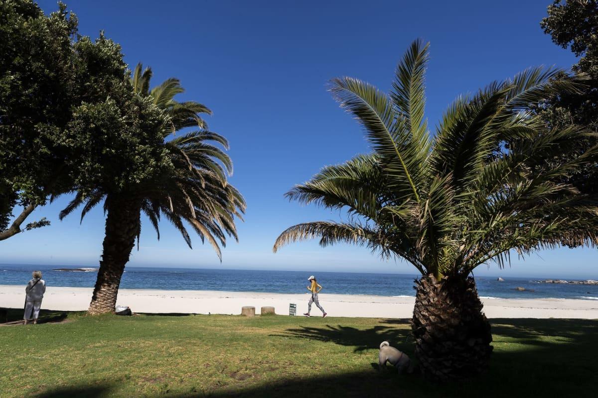 Autio hiekkaranta, viereisellä viheralueella on pari ihmistä.