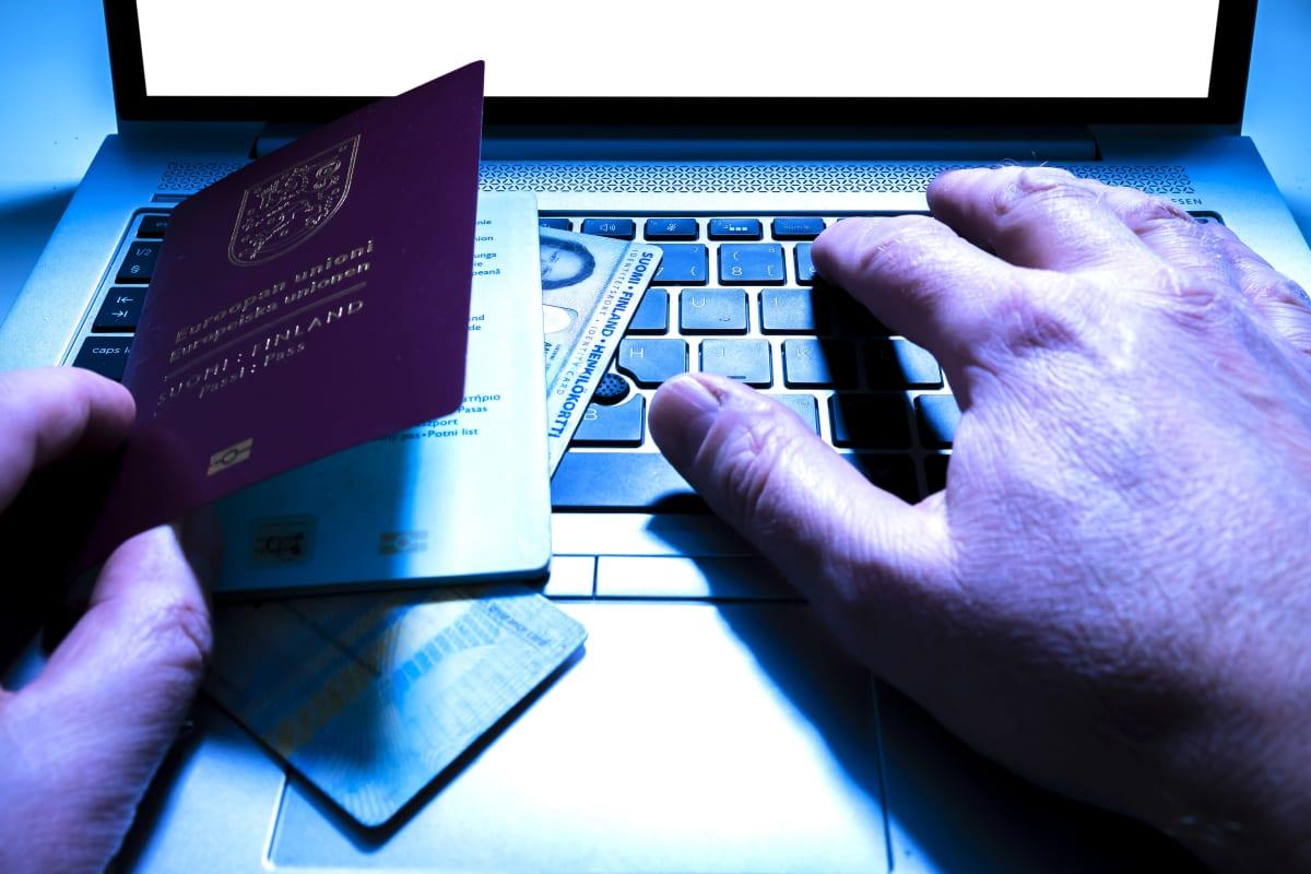 Miehen kädet sekä passi ja henkilöllisyystodistuksia tietokoneen näppäimistöllä.