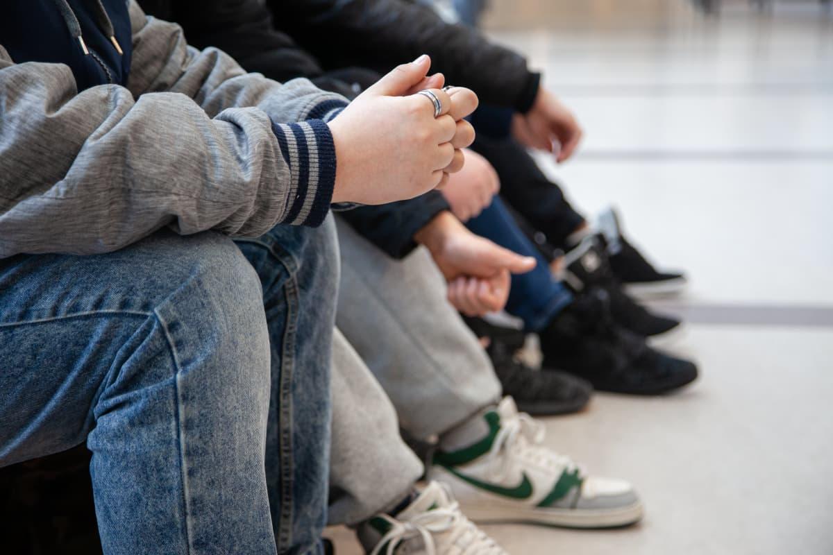 Anonyymeja 7.-luokkalaisia poikia istumassa Lauritsalan koulun käytävällä.
