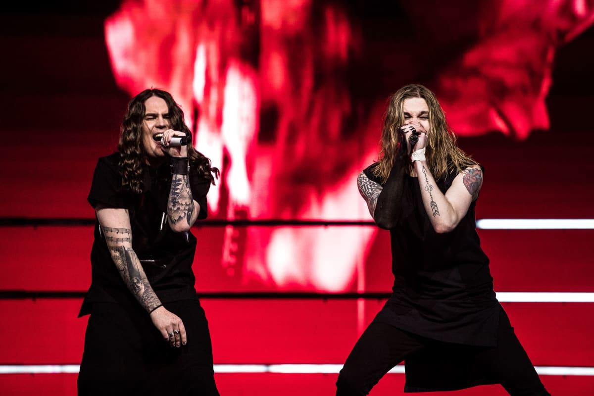 Kaksi Blind Channelin jäsentä laulaa mikrofoniin lavalla, takana voimakas punainen tausta. Molemmilla miehillä on pitkät hiukset ja mustat asut.