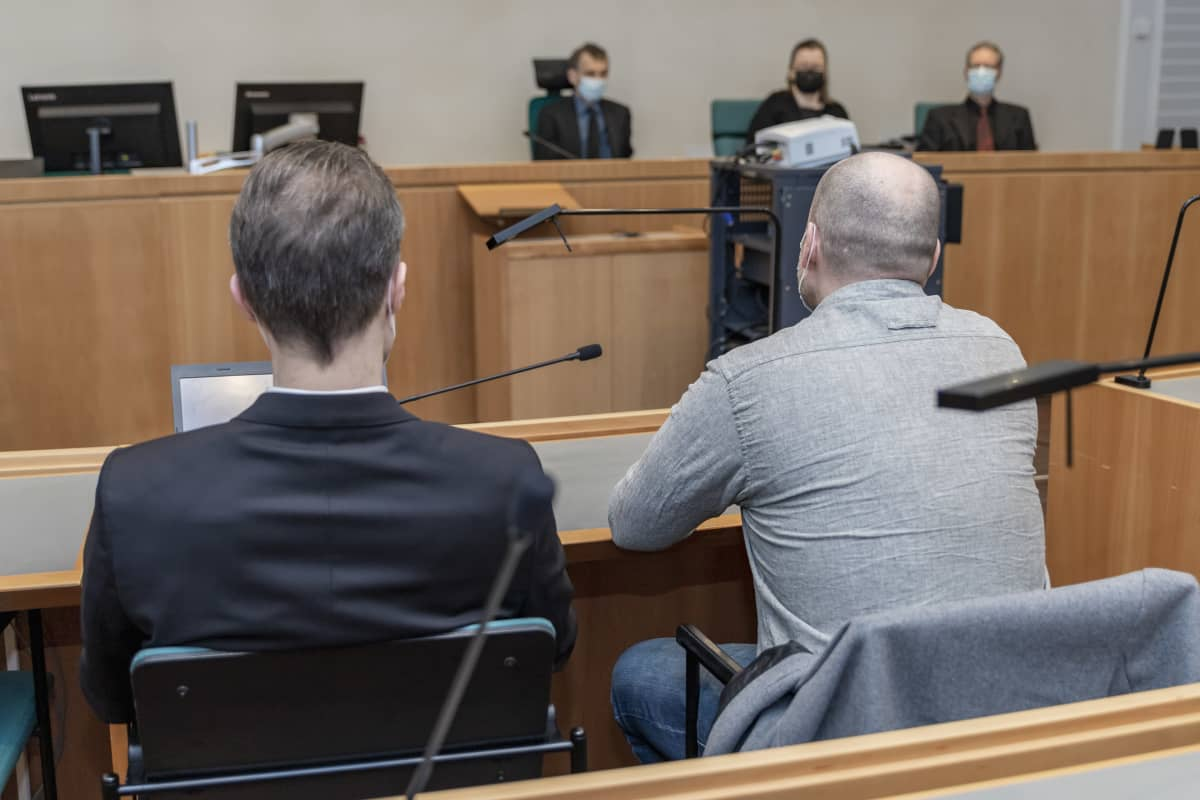 Syytetty istuu asianajajansa kanssa oikeussalissa.