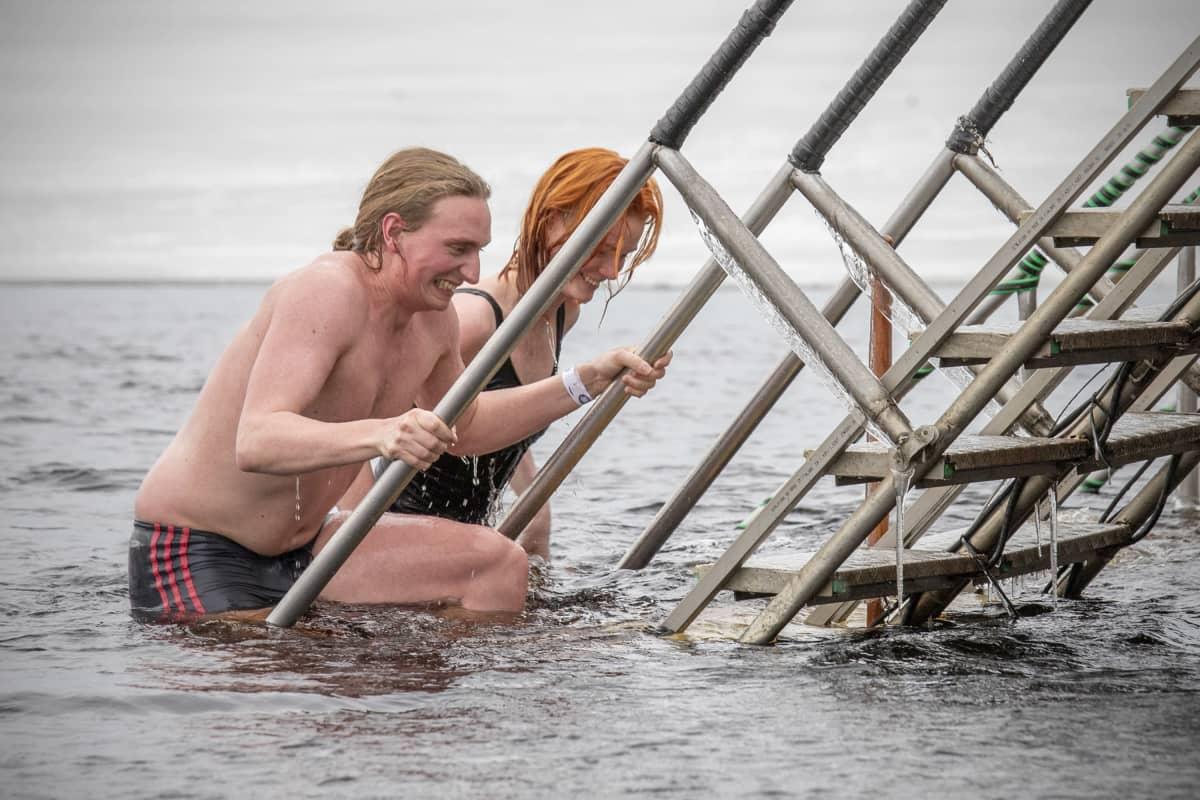 Juhana Jämsen ja Auli Sipola nousevat avannosta portaita pitkin.