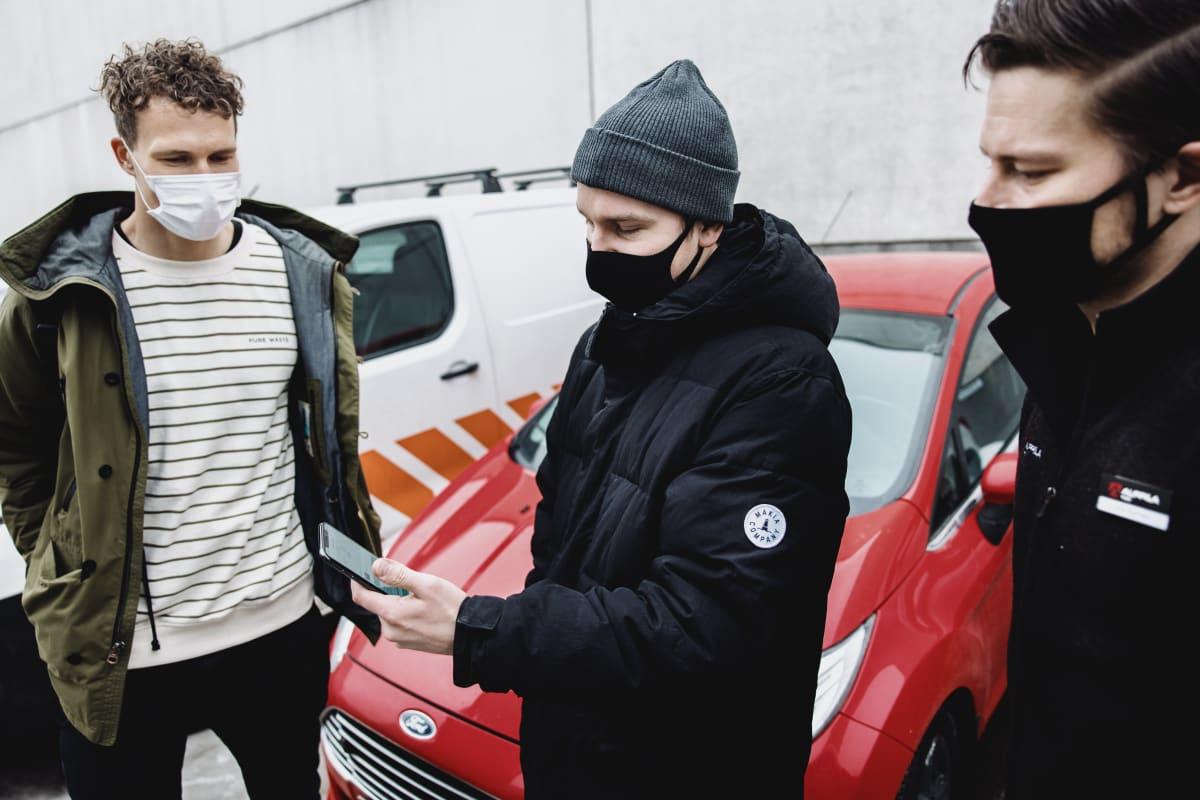 Gomoren edustaja Boris Perkiö (vas.) ja mekaanikko Jani Kivinen (oik.) seuraavat, kuinka Huotilaiselta sujuu auton etähallinta puhelinsovelluksella.